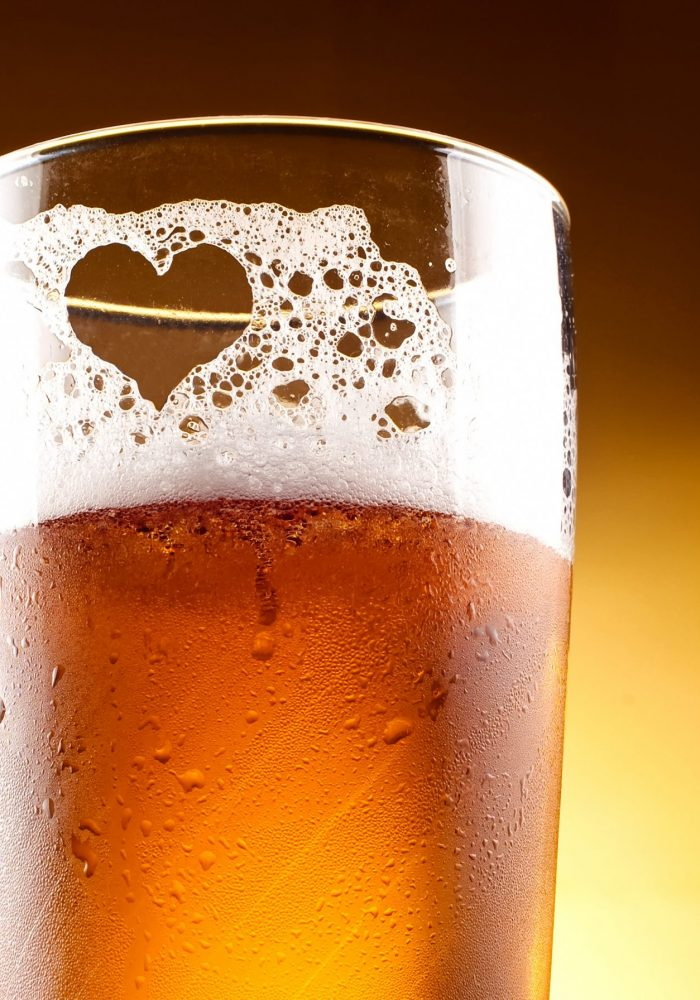 Glass of beer with the heart represented with froth close up over yellow background